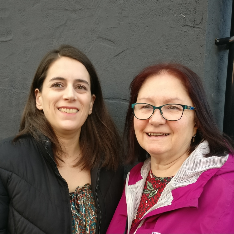 Two dark haired women against a black wall, looking at the camera and smiling